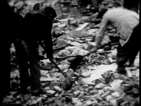 the destruction caused by fascist bombers over madrid / rubble and bombed out buildings / people clearing rubble - air raid点の映像素材/bロール