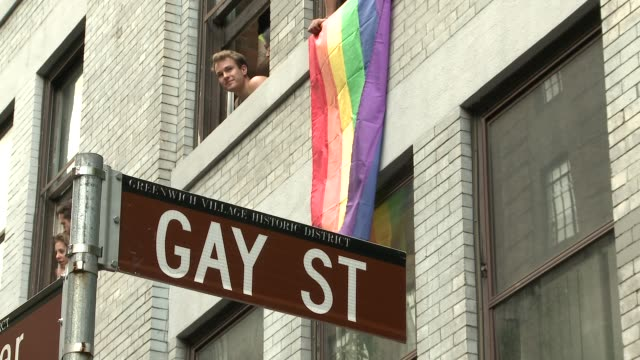 the diet coke float heads through greenwich village / various scenes of spectators enjoying the parade from the route and from apartment windows - rainbow flag stock videos & royalty-free footage