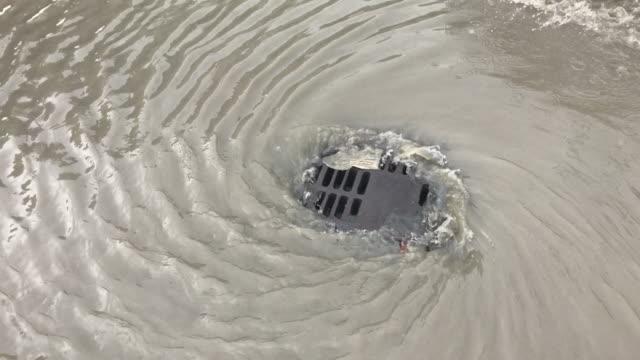 vídeos de stock, filmes e b-roll de o fluxo de inundação de água suja para drenagem depois de chover - drenagem