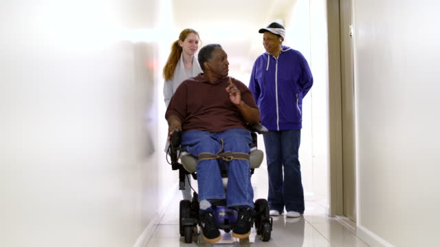 the disabled african-american man in wheelchair, accompanied with black woman and white teenager girl, in the corridor of the residential living building in bronx - community outreach stock videos & royalty-free footage
