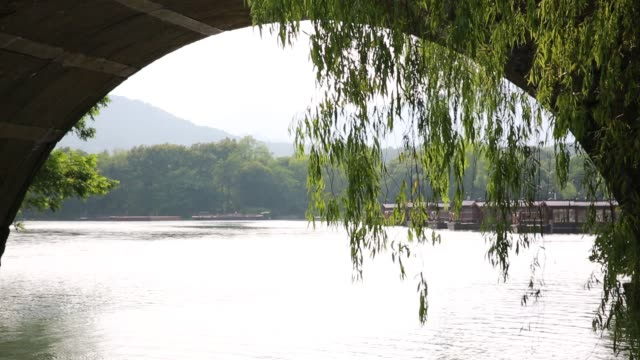 the dock seen from an arch of a stone bridge on west lake,hangzhou,china - arch bridge stock videos & royalty-free footage