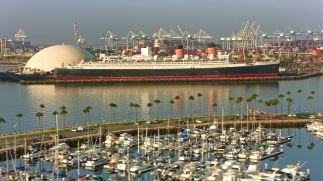 stockvideo's en b-roll-footage met aerial the docked ship queen mary and the long beach cruise terminal at sunrise - long beach californië