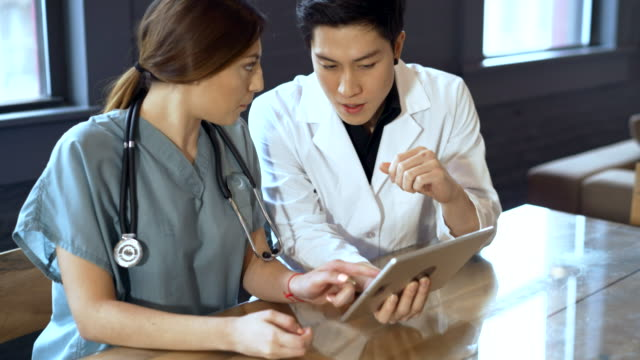 the doctor and the nurse reviewing some info on the tablet - nurse stock videos & royalty-free footage
