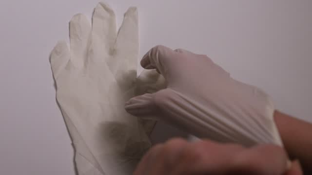 the doctor puts on a glove on white background. vaccine and syringe injection. prevention,immunization and treatment from corona virus infection - ago parte della pianta video stock e b–roll