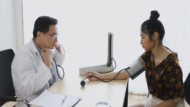The Doctor using blood pressure gauge for checking to women patients in his office at Hospitals