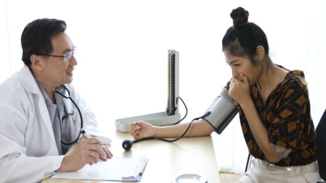 vídeos y material grabado en eventos de stock de el doctor con medidor de presión de la sangre para controlar a los pacientes de las mujeres en su oficina en los hospitales - miembro humano