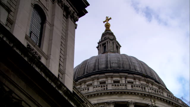 the dome of st. paul's cathedral contrasts against a cloudy blue sky. - religious equipment stock videos & royalty-free footage