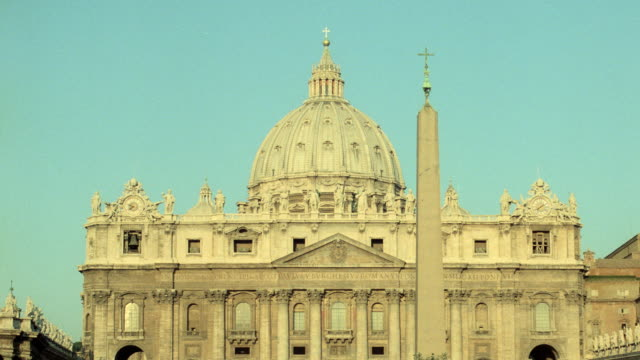 vídeos de stock e filmes b-roll de the dome of st. peter's basilica contrasts against a pale blue sky in vatican city. - obelisk