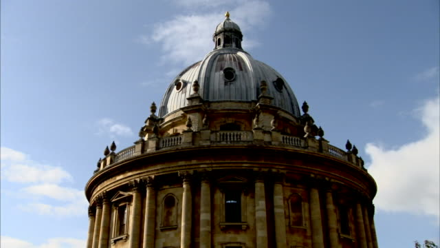the dome of the university of oxford's bodleian library contrasts against a cloudy blue sky. - oxfordshire stock videos & royalty-free footage