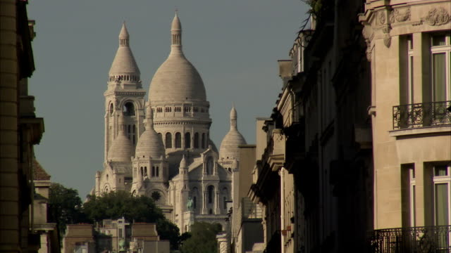 the domes of the sacre coeur rise above the nearby streets of paris. available in hd. - basilique du sacre coeur montmartre stock videos & royalty-free footage