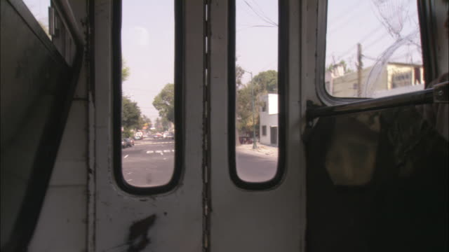 The door of a moving bus overlooks neighborhood streets.