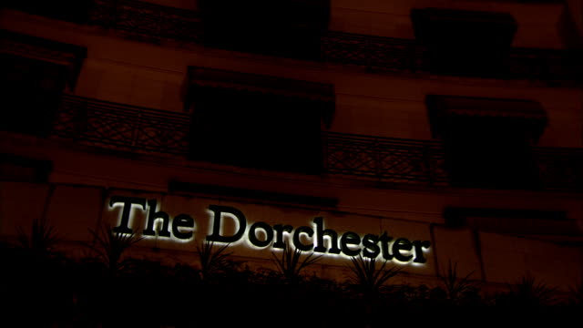 MS POV The Dorchester Hotel entrance on Park Lane at night / Mayfair, London, England