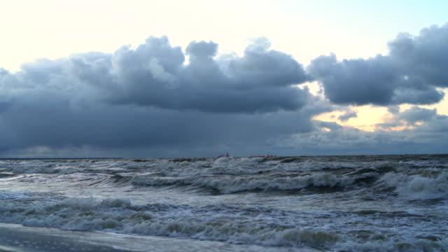 De dramatische bewolkte hemel over de Baltische zee bij de zonsondergang, met de schepen aan de horizon.
