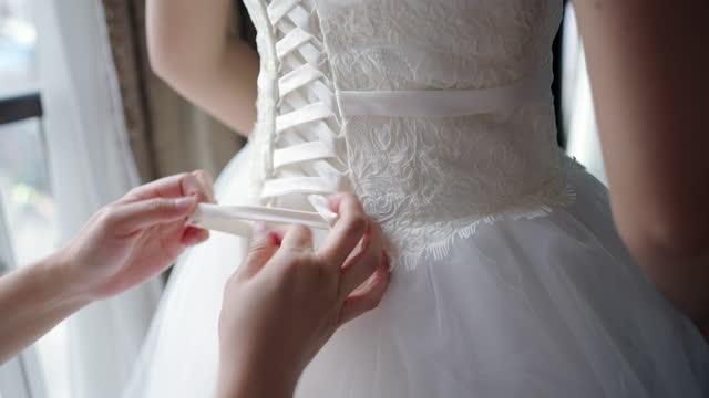 ドレスメーカーは、体の周りの測定し、ウェディングドレスを試着しています。 - 白のドレス点の映像素材/bロール