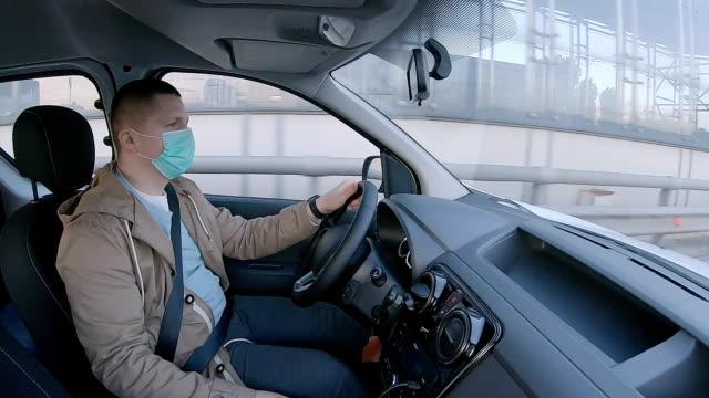 vídeos y material grabado en eventos de stock de el conductor conduce un coche con una máscara protectora para la cara. - taxista
