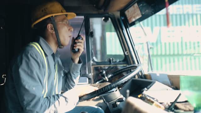 the driver uses thewalkie talkie to communicate with the company - transportmedel bildbanksvideor och videomaterial från bakom kulisserna