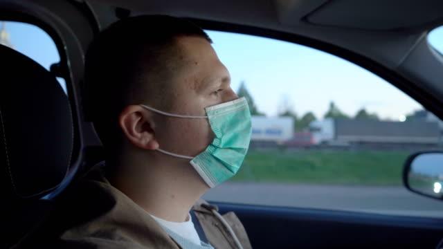 das gesicht des fahrers in einer schützenden gesichtsmaske während der fahrt. - mundschutz stock-videos und b-roll-filmmaterial