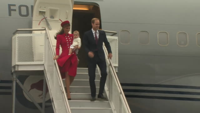 the duke and duchess of cambridge carrying baby prince george walking down steps of plane on arrival in wellington new zealand - baby waving stock videos & royalty-free footage