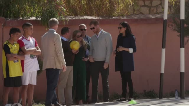 The Duke and Duchess of Sussex visit a local secondary school in Asni Morocco where they watch children playing football and pose for a group photo