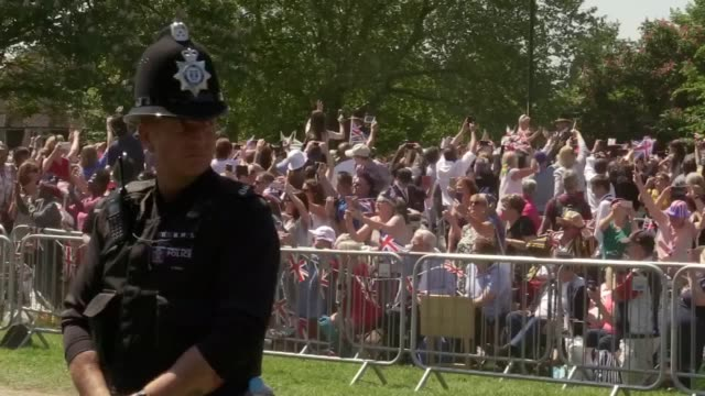 The Duke and Duchess of Sussex wave to crowds as they travel through Windsor on their royal wedding procession