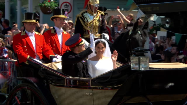 The Duke and Duchess of Sussex wave to crowds as they travel through Windsor after their wedding
