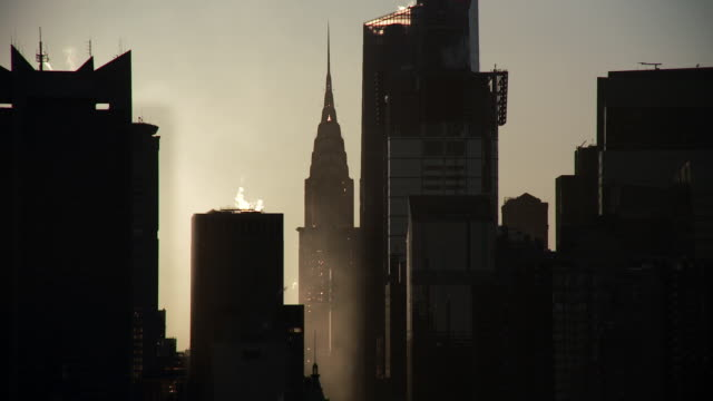 vídeos de stock e filmes b-roll de the early morning sun shining dimly and slowly revealing detail on the silhouette of the new york city skyline showing the chrysler building - prédio chrysler