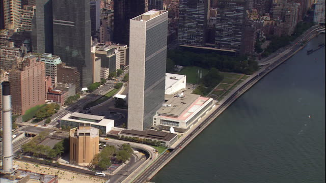 the east river passes by the united nations building in manhattan, new york city. - united nations building stock videos and b-roll footage