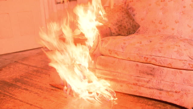 the edge of a living room sofa is engulfed with flames. - burning stock videos & royalty-free footage