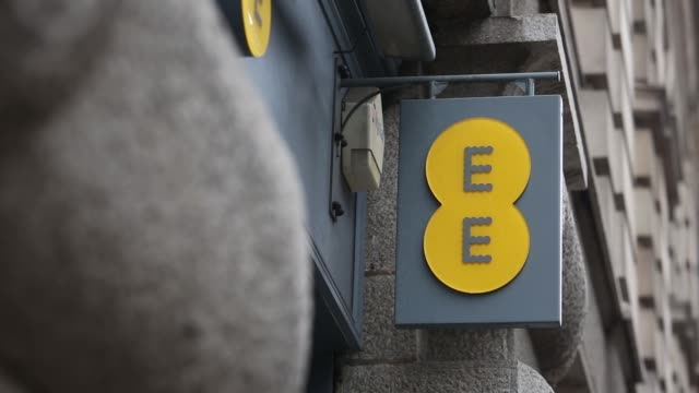 the ee logo hangs from an ee mobile phone store in london, uk, on wednesday, nov 26 an ee, orange, t-mobile banner on the window of the store,... - basildon stock videos & royalty-free footage