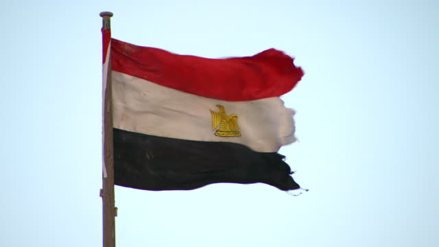 The Egyptian flag flies from a flagpole.