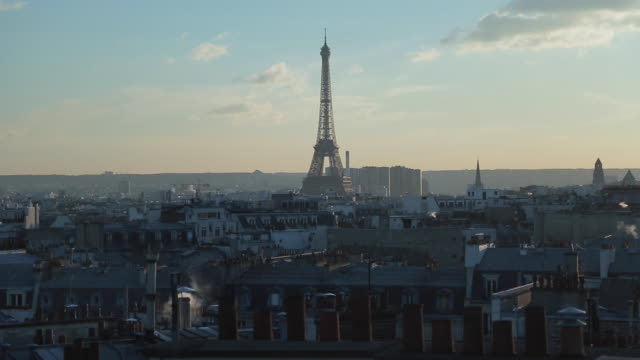 The Eiffel tower in Paris, France, with rooftops and lens flares
