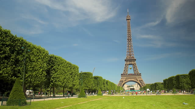 the eiffel tower on a warm summer day seen from the champs de mars on june 7 in paris, france. the park is dominated by the huge eiffel tower, one of... - tower stock-videos und b-roll-filmmaterial