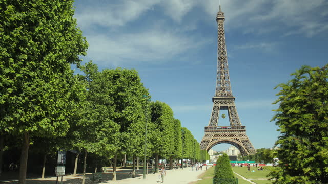 the eiffel tower on a warm summer day seen from the champs de mars on june 7 in paris, france. the park is dominated by the huge eiffel tower, one of... - copy space stock videos & royalty-free footage