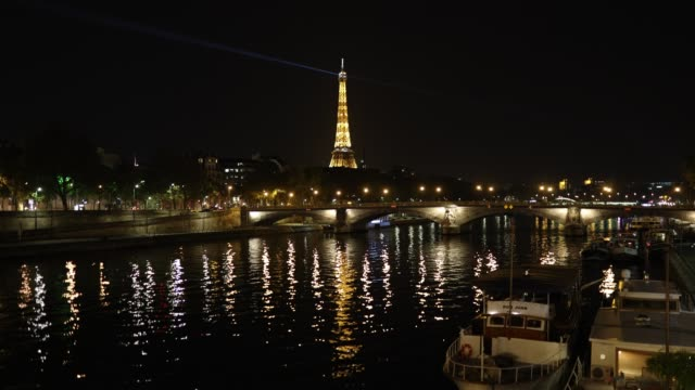 the eiffel tower shines and is reflected on the seine at curfew time on october 18, 2020 in paris, france. france. the french government has imposed... - politics illustration stock videos & royalty-free footage