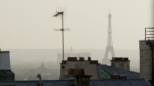 the eiffel tower soars above the skyline of paris. available in hd. - smog stock videos & royalty-free footage
