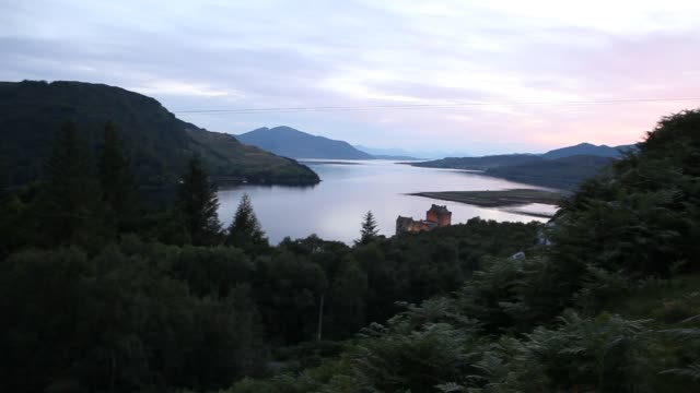 the eilean donan castle on an island in loch duich is only accessible via a stone bridge at sunset - dornie stock videos & royalty-free footage