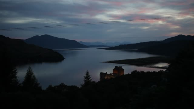 the eilean donan castle on an island in loch duich is only accessible via a stone bridge at sunset - see loch duich stock-videos und b-roll-filmmaterial