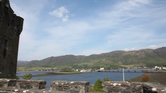 vídeos de stock, filmes e b-roll de the eilean donan castle on an island in loch duich is only accessible via a stone bridge - loch