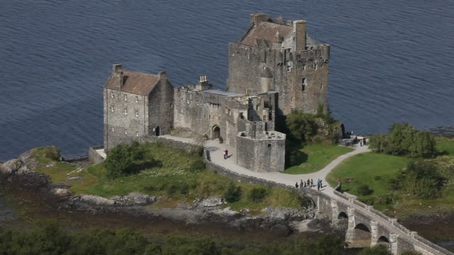 the eilean donan castle on an island in loch duich is only accessible via a stone bridge - dornie stock videos & royalty-free footage