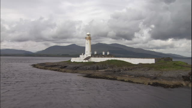 vídeos de stock e filmes b-roll de the eilean musdile lighthouse overlooks the sound of mull in scotland. - ilha mull