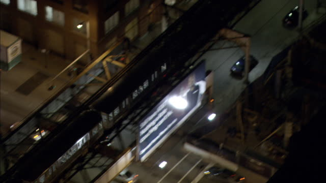 the el train transit system carries passengers on an elevated track through downtown chicago at night. - chicago elevated stock-videos und b-roll-filmmaterial