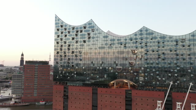 stockvideo's en b-roll-footage met the elbphilharmonie concert hall building stands in the hafencity quarter at sunset during the coronavirus pandemic on august 12, 2020 in hamburg,... - quarter