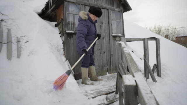 the elderly man cleans snow around their wooden house - schneebedeckt stock-videos und b-roll-filmmaterial