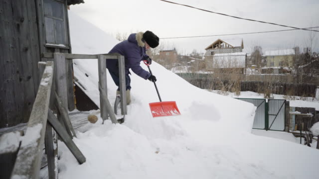 the elderly man cleans snow around their wooden house - digging stock videos & royalty-free footage