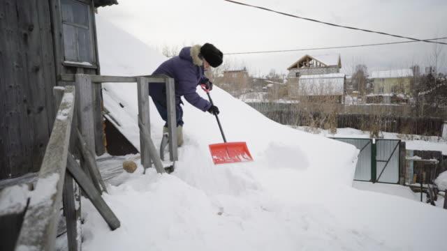 stockvideo's en b-roll-footage met the elderly man cleans snow around their wooden house - digging