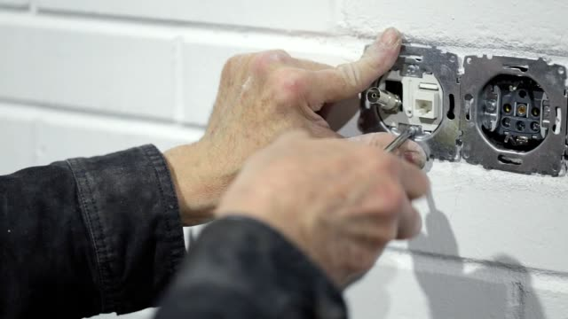 the electrician fixes the television cable in the wall. - cable television stock videos & royalty-free footage