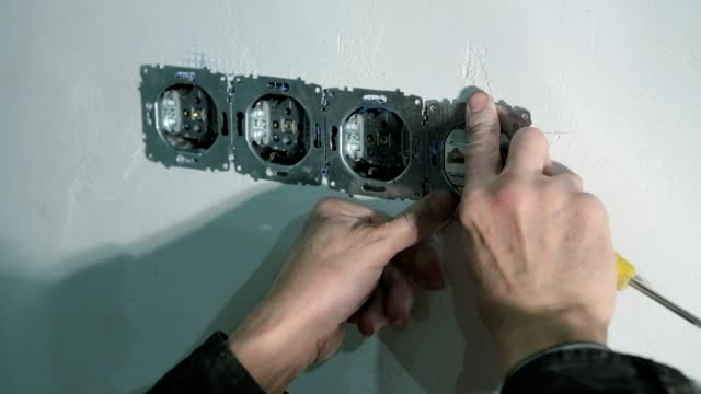 The electrician fixes the television cable in the wall.