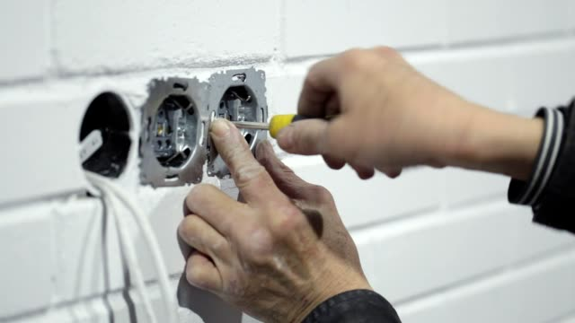 the electrician installs electrical outlets. - repairing stock videos & royalty-free footage