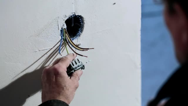 the electrician installs the light switch. - cable stock videos & royalty-free footage