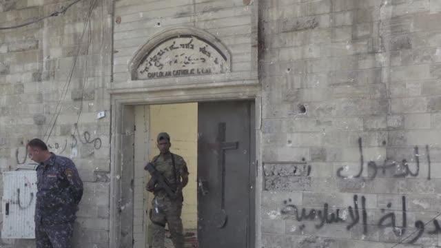 the elegant columns of a west mosul church stand plastered with islamic state group propaganda after the jihadists infamous religious police took... - propaganda bildbanksvideor och videomaterial från bakom kulisserna